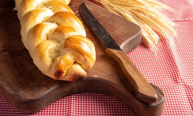 Zelfgebakken brood, gevlochten brood op hout en een rood en wit geruit tafelkleed, een mes en een takje tarwe.