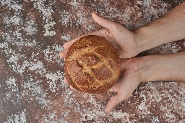 Zelfgebakken brood in de hand van de kok.