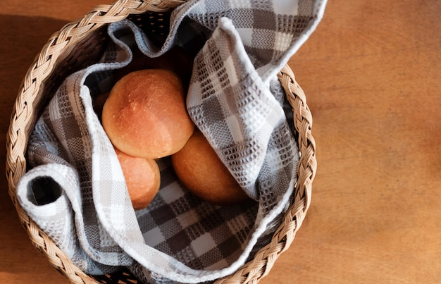Zelfgebakken brood in de mand op de houten tafel, ontbijttijd, bovenaanzicht