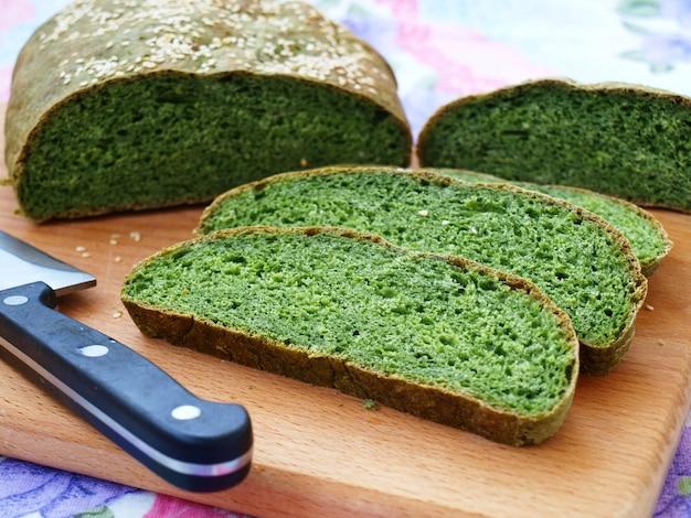 Zelfgebakken brood met brandnetels groen, in plakjes gesneden en bevindt zich op een houten plank, horizontale oriëntatie
