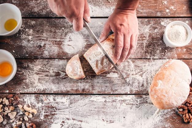 Zelfgebakken brood snijden op de keukentafel