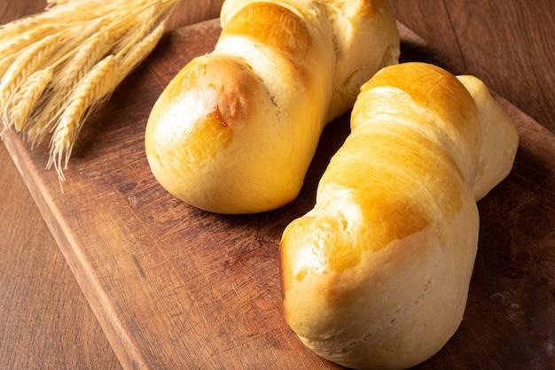 Zelfgebakken brood, twee mooie huisgemaakte broden op hout en een takje tarwe.