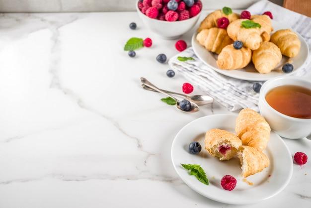 Zelfgebakken croissants met frambozen en bosbessen