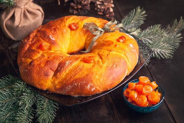 Zelfgebakken kerstbrood in een vorm van adventskrans van gistdeeg met oranje gekonfijte vruchten op achtergrond van dennentakken.