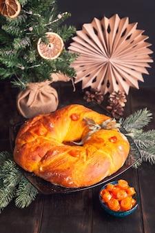 Zelfgebakken kerstbrood in een vorm van adventskrans van gistdeeg met oranje gekonfijte vruchten op de achtergrond van de kerstboom.