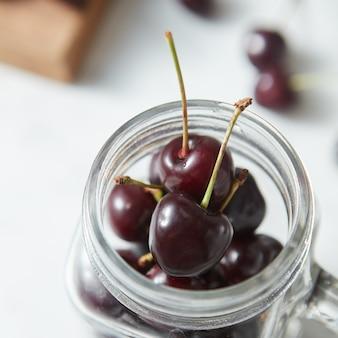 Zelfgekweekte natuurlijke verse bessen voor het koken van jam in een glazen beker op de keukentafel. ondiepe scherptediepte.