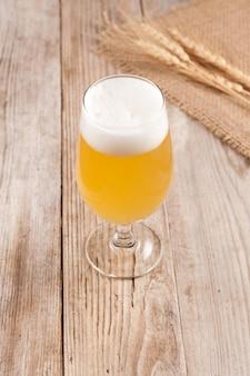 Zelfgemaakt ambachtelijk bier in een glas op een oude houten tafel