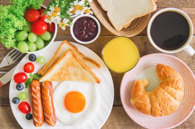 Zelfgemaakt amerikaans ontbijt met zwarte koffie en jus d'orange.