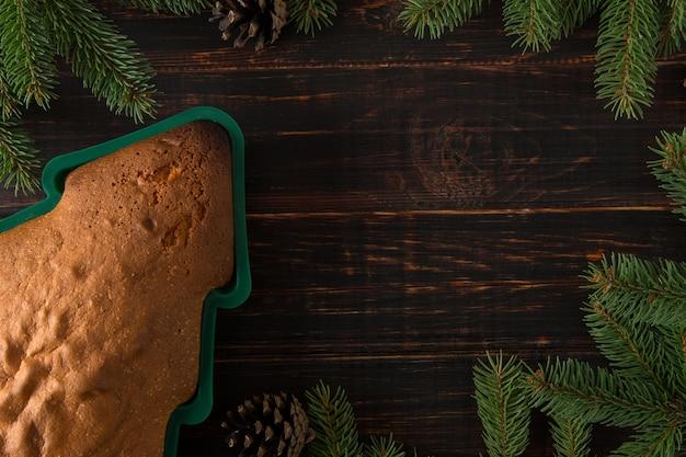 Zelfgemaakt bakken, koekjes in de vorm van een kerstboom, dennentakken en decoraties op een houten tafel. bovenaanzicht, plat gelegd.