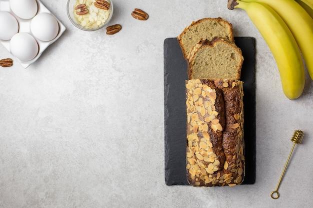 Zelfgemaakt bananenamandelbrood met pecannoten en ingrediënten, in een ovenschaal, op een houten bord, lichte ondergrond