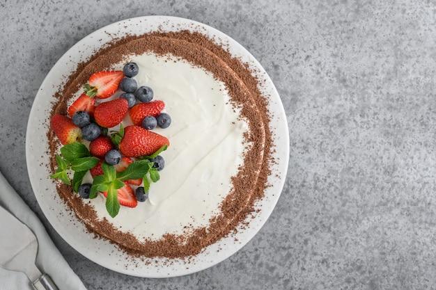 Zelfgemaakt cakekoekje met mascarpone verfraaid geraspte chocolade, verse aardbeien en bosbessen op grijs