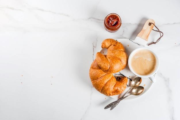 Zelfgemaakt continentaal ontbijt, koffie croissants. jam op witte marmeren tafel, copyspace bovenaanzicht