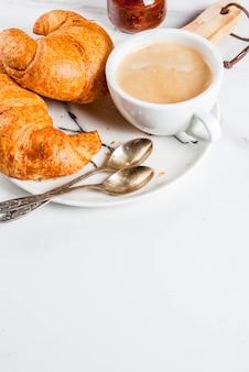 Zelfgemaakt continentaal ontbijt, koffie croissants. jam op witte marmeren tafel, copyspace