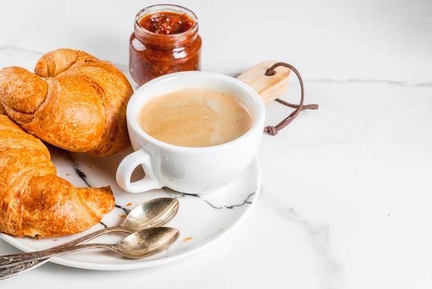 Zelfgemaakt continentaal ontbijt, koffie croissants. jam op witte marmeren tafel, kopie ruimte