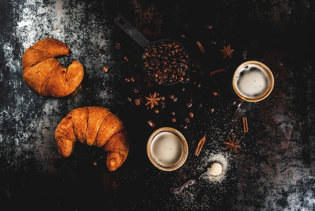Zelfgemaakt continentaal ontbijt, koffie met kruiden, rietsuiker, croissants. jam op een zwarte roestige metalen tafel, bovenaanzicht copyspace