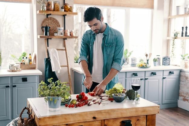 Zelfgemaakt diner. knappe jongeman in vrijetijdskleding die groenten snijdt terwijl hij thuis in de keuken staat