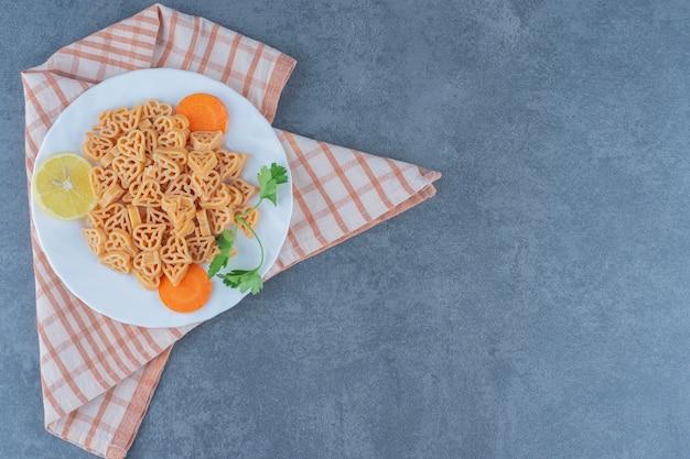Zelfgemaakt diner met hartvormige pasta op witte plaat.
