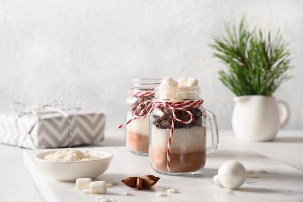 Zelfgemaakt eetbaar kerstcadeau in glazen pot voor het maken van chocoladedrank.