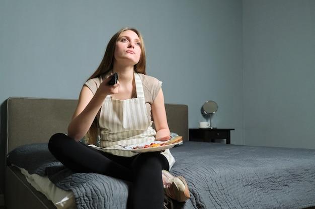 Zelfgemaakt eten op bord in handen van jonge vrouw, meisje zittend op bed met afstandsbediening tv kijken en eten. vrouw rust thuis