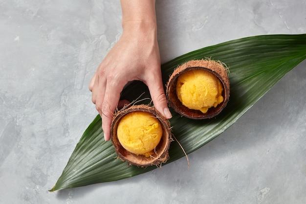 Zelfgemaakt fruitijs in een kokosnootschil op een palmblad op een grijze betonnen tafel. de hand van een meisje pakt een schelp met ijs. kopieer ruimte voor uw tekst. bovenaanzicht