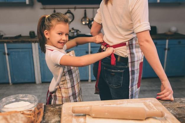 Zelfgemaakt gebak koken. de gelukkige houdende van familie bereidt samen bakkerij voor. moeder en kind dochter meisje koken koekjes en hebben plezier in de keuken. jurk schorten