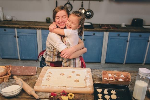 Zelfgemaakt gebak koken. de gelukkige houdende van familie bereidt samen bakkerij voor. moeder en kind dochter meisje koken koekjes en hebben plezier in de keuken. kind samen koekjes bakken