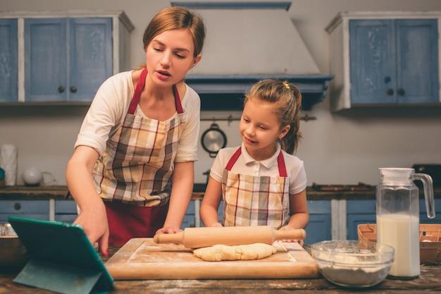 Zelfgemaakt gebak koken. de gelukkige houdende van familie bereidt samen bakkerij voor. moeder en kind dochter meisje koken koekjes en hebben plezier in de keuken. recepten zoeken op de tablet