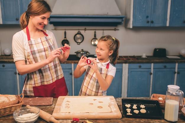 Zelfgemaakt gebak koken. de gelukkige houdende van familie bereidt samen bakkerij voor. moeder en kind dochter meisje koken koekjes en hebben plezier in de keuken. rol het deeg uit. mallen van deeg.