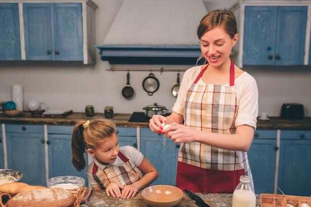Zelfgemaakt gebak koken. de gelukkige houdende van familie bereidt samen bakkerij voor. moeder en kind dochter meisje koken koekjes en hebben plezier in de keuken. rol het deeg uit. smash eieren