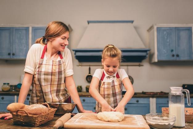 Zelfgemaakt gebak koken. de gelukkige houdende van familie bereidt samen bakkerij voor. moeder en kind dochter meisje koken koekjes en hebben plezier in de keuken. rol het deeg uit.