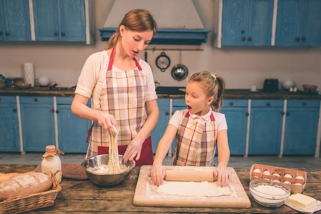 Zelfgemaakt gebak koken. de gelukkige houdende van familie bereidt samen bakkerij voor. moeder en kind dochter meisje koken koekjes en plezier in de keuken. rol het deeg uit.