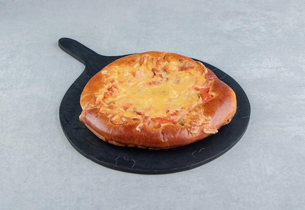 Zelfgemaakt gebak met kaas op een zwart bord.