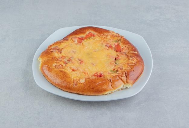 Zelfgemaakt gebak met kaas op witte plaat.