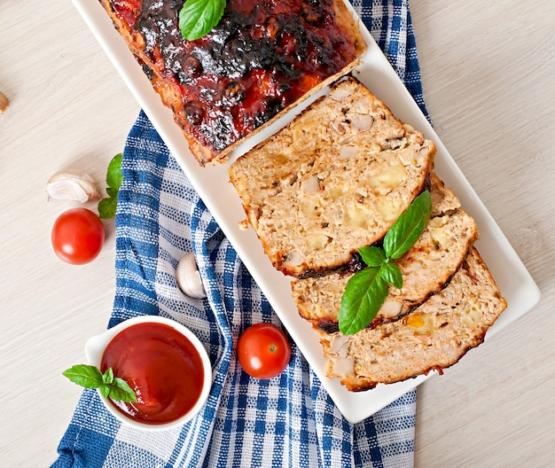 Zelfgemaakt gehaktbrood met ketchup en basilicum