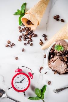 Zelfgemaakt koffie-ijs, geserveerd met koffiebonen en muntblaadjes, met ijshoorntjes en lepels op de foto. witte marmeren achtergrond,