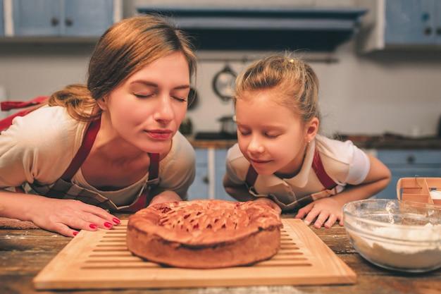 Zelfgemaakt koken. de gelukkige houdende van familie bereidt samen bakkerij voor. moeder en kinddochter die pret in de keuken hebben. ze snuiven vers gebakken zelfgemaakte taart.