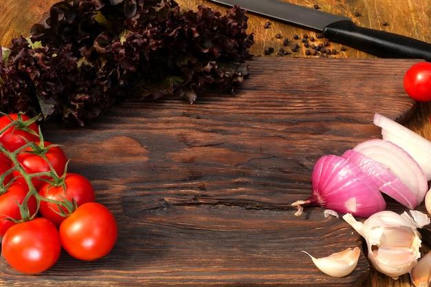 Zelfgemaakt koken. producten voor heerlijk eten. groenten: tomaten, sla, ui, knoflook, liggen op een houten keukenbord.