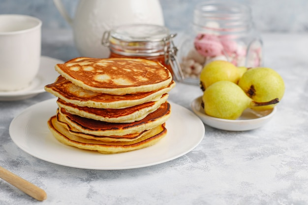 Zelfgemaakt ontbijt: amerikaanse pannenkoeken geserveerd met peren en honing met een kopje thee op beton. bovenaanzicht en kopiëren