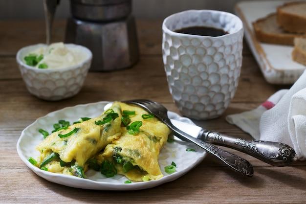 Zelfgemaakt ontbijt van omelet met asperges en uien en warme koffie. rustieke stijl.