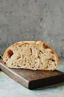 Zelfgemaakt vers brood gemaakt van tarwe en volkoren meel op een grijze muur.