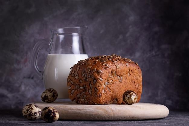 Zelfgemaakt vers brood met zonnebloempitten en melk op een houten bord