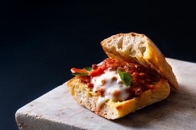 Zelfgemaakt voedselconcept organische bolognese sandwich van het grill artisanale brood op zwarte