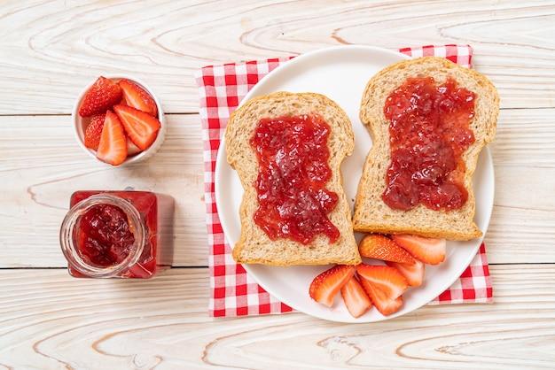 Zelfgemaakt volkorenbrood met aardbeienjam en verse aardbeien