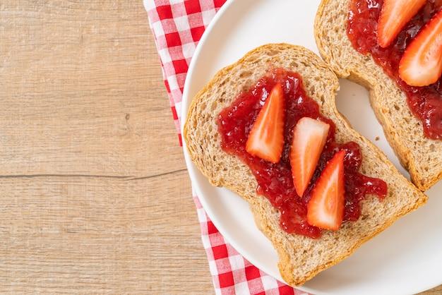 Zelfgemaakt volkorenbrood met aardbeienjam en verse aardbeien Premium Foto