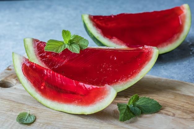 Zelfgemaakt watermeloen en muntdessert. gelei in een watermeloen op een lichte achtergrond.