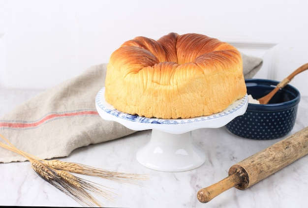 Zelfgemaakt wolbroodje, virale japanse brioche shokupan hokkaido melkbrood met prachtige textuur zoals wol. geserveerd op witte taartplateau met kopieerruimte