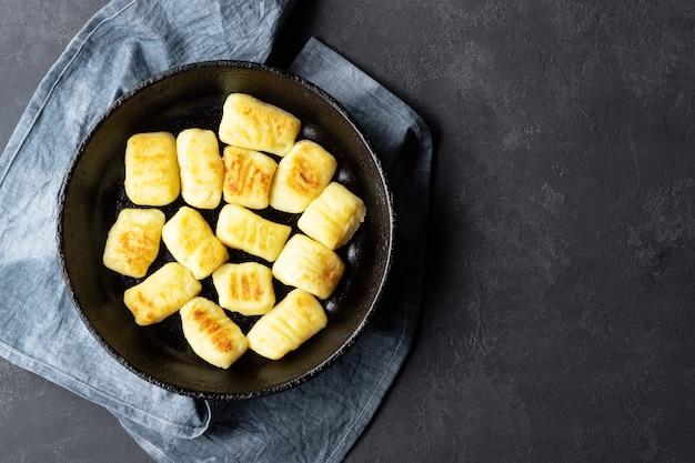 Zelfgemaakte aardappel gnocchi. plat leggen. zwarte achtergrond.