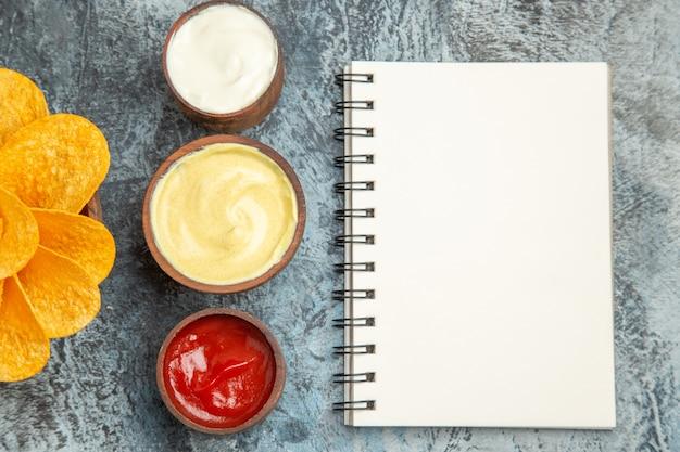 Zelfgemaakte aardappelchips versierd als bloemvormig en zout met ketchupmayonaise en notitieboekje op grijze tafel