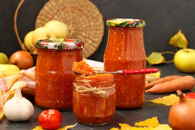 Zelfgemaakte adzhika met tomaten, appels en wortelen in potten op een donkere muur, oogsten voor de winter