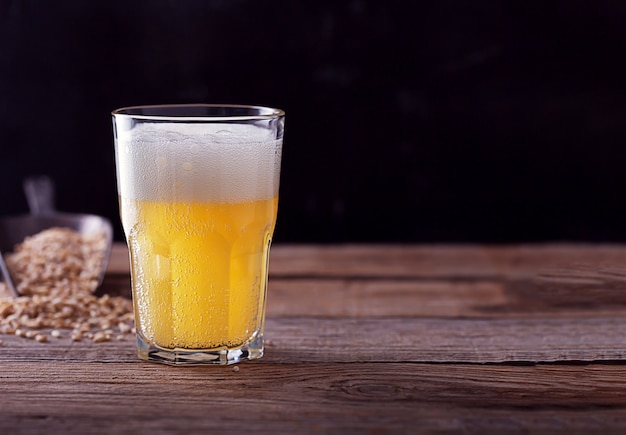 Zelfgemaakte ambachtelijke bier in een glas, donkere houten tafel
